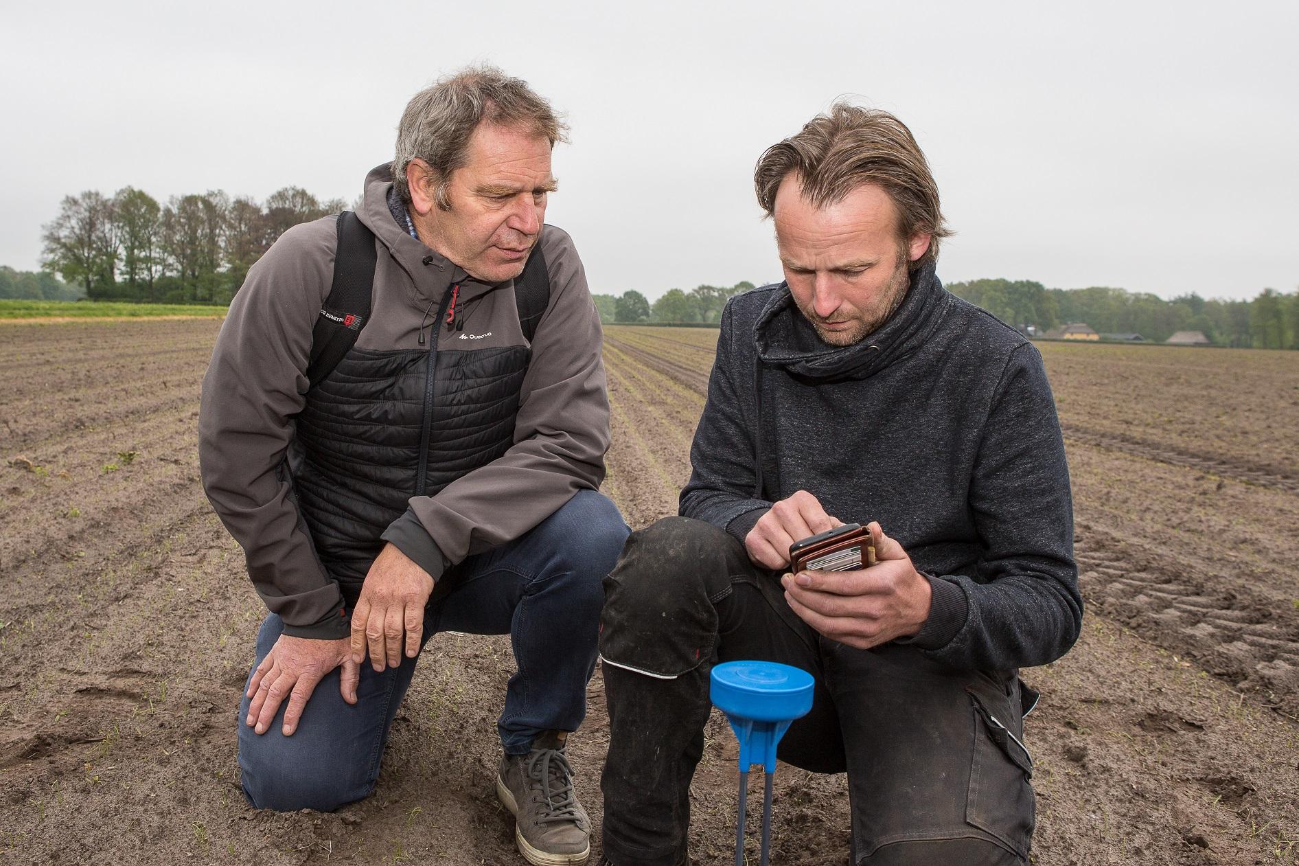 Pieter van Leeuwen-Boomkamp in gesprek met WUR expert Jean-Marie Michielsen bij een vochtensor in de uien.