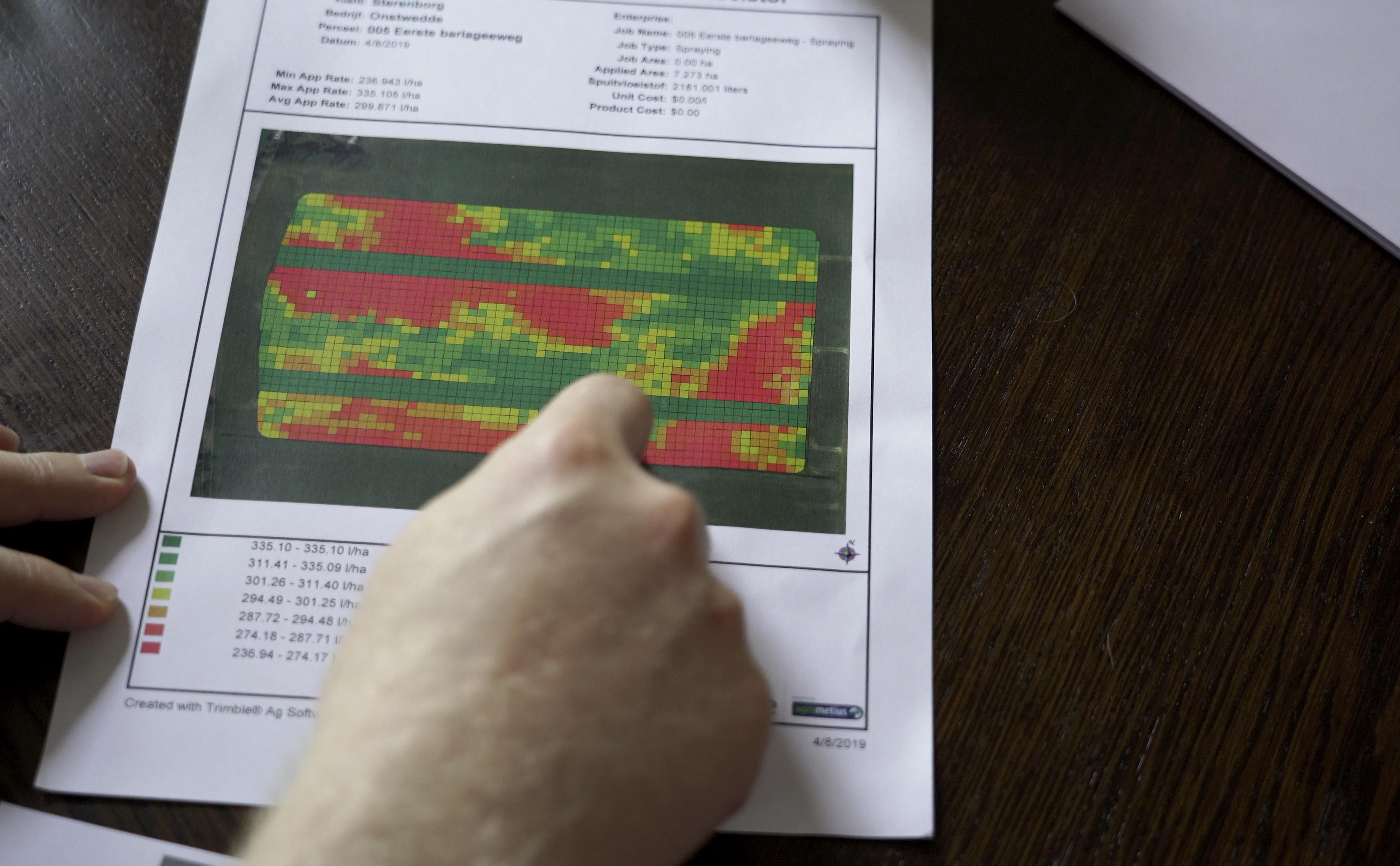De bodemherbiciden taakkaart voor perceel Eerste Barlageweg met 3x3 m grote grids en variatie in dosering van 235 tot 335 l/ha. Nanne wijst een van de twee 9 m brede referentiestroken aan die de standaarddosering (300 l/ha) kregen.